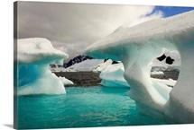 Sculpted icebergs under clouds near Couverviller Island, Antarctica