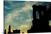 Skyward view of the Brooklyn Bridge silhouetted against a blue sky