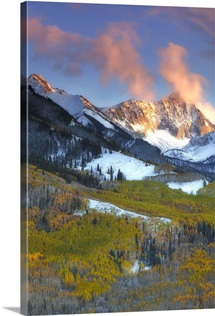 Sunlight on snow-covered mountains and golden aspen trees in a valley