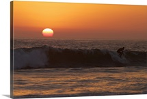 Surfer riding a wave at sunset over the Pacific Ocean