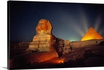 The Great Sphinx and one of a trio of pyramids at dusk with artificial lighting effects