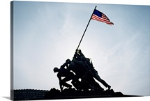 The Iwo Jima Memorial statue, silhouetted with flag flying