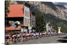 The USA Pro Cycling Challenge race passing through a rustic downtown