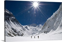 Three climbers cross a snowfield on the way up to Everest