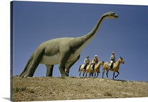Tourists ride past a life-size dinosaur statue, Dinosaur Park, South Dakota