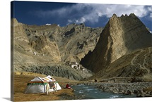 Trekker writes in diary beside Tibetan tent, Himalayas, India