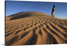 Tuareg guide Yahya stands on a sand dune