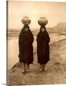 Two Zuni girls pose beside the river, water jugs atop their heads