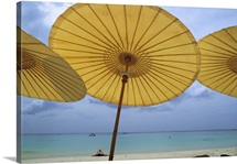 View of the beach from underneath yellow umbrellas at the Amanpuri Hotel, Phuket, Thailand