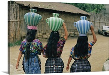 Village women carrying a water jugs, Central America