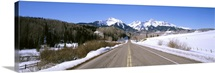 Highway in front of snowcapped mountains, Telluride, Colorado