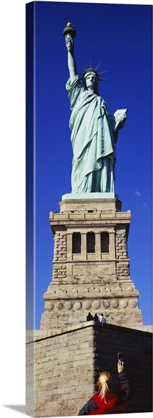 Low angle view of a tourist taking a picture of a statue, Statue of Liberty, Liberty State Park, Liberty Island, New York City, New York State