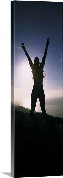 Low angle view of a young woman exercising on a hill