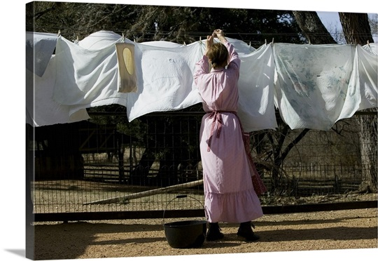 Rear View Of A Woman Drying Clothes On A Clothesline