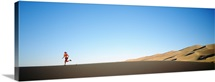 Rear view of a woman running in the desert, Great Sand Dunes National Monument, Colorado
