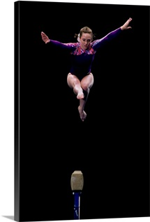 Female gymnast performing on the balance beam.