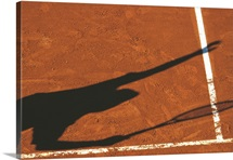 Shadow of tennis player serving on clay court