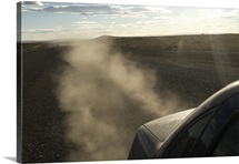 Dust kicks up from behind of car in Patagonia, Southern Argentina