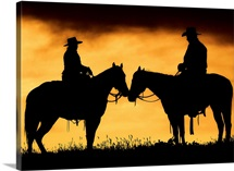 Cowboy and cowgirl on horseback in silhouette at sunset