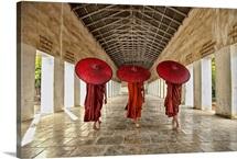 monks walking with parasols in monastery, Mandalay, Burma