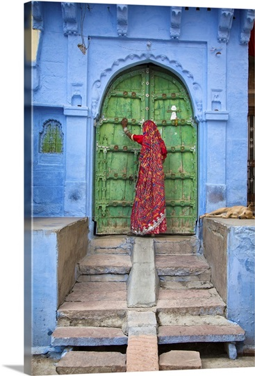 Woman knocking on door in the Blue City of Jodphur, India