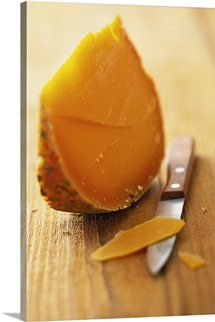 Mimolette (semi-hard cheese) on wooden background with knife
