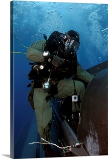A Navy SEAL climbs aboard a SEAL Delivery vehicle before launching from a submarine