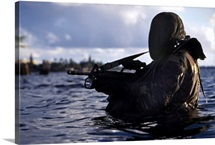 A Navy SEAL emerges from underwater during a training exercise