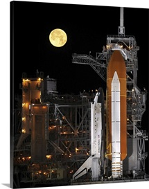 A nearly full Moon sets as Space Shuttle Discovery sits atop the launch pad