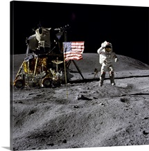 An astronaut stands next to the American flag during an Apollo 16 moonwalk