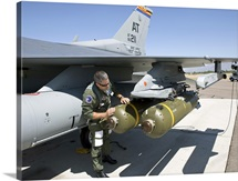 An F-16 pilot conducts a preflight check on a weapon prior to a mission