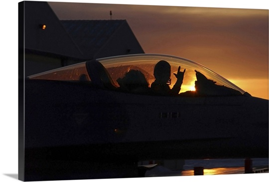 An F16 Fighting Falcon Fighter Pilot gives the mission accomplished sign while taxiing