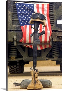 An M16A2 service rifle a pair of boots and a helmet stand in tribute to a fallen soldier