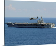 An MH 60S Seahawk helicopter flies over USS George H.W. Bush