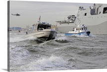 Crews from the coast guard and police departments escort USS New York