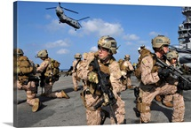 Marines position themselves on the flight deck of USS Makin Island