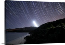 Moonset and star trails behind the Arrabida Mountain range in Portugal