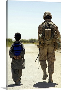 Rear view of US Marine walking through Nawa bazaar with an Afghan boy in Afghanistan