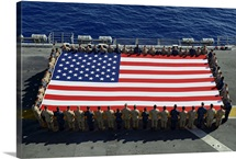 Sailors and Marines display the national ensign aboard USS Kearsarge