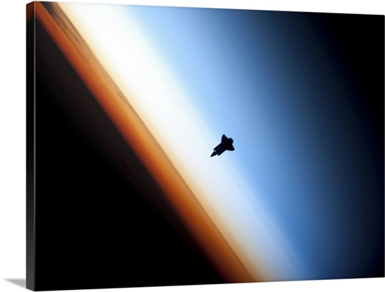 Silhouette of space shuttle Endeavour over Earths colorful horizon