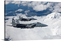 Two F-15 Eagles fly past snow-capped peaks in Central Oregon