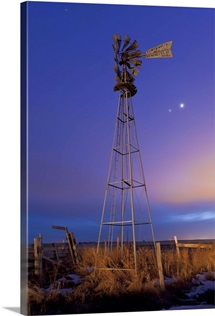 Venus and Jupiter are visible behind an old farm water pump windmill, Alberta, Canada