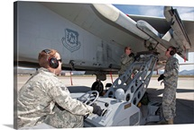 Weapons crew prepare to load an AIM-120 missile on an F-15 Eagle