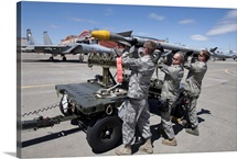 Weapons crew prepare to load an AIM-9X missile on an F-15 Eagle