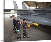 Weapons crew prepare to load an AIM-9X missile onto an F-15 Eagle