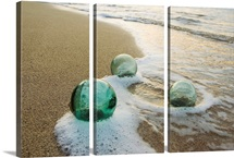 Three Glass Fishing Floats Roll On The Sandy Shoreline With Ripples Of Water And Seafoam