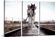 A military dog handler uses an over-the-shoulder technique to carry his dog