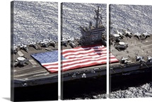 Personnel participate in a flag unfurling rehearsal on the flight deck aboard USS Nimitz