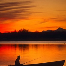 Silhouetted Fisherman sits in his boat at Sunset
