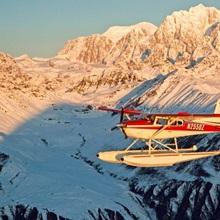 View of a Cessna 185 floatplane in Alaska Range over Ruth Glacier at sunset